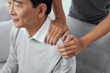 Asian old man shoulder pain, sitting on sofa , son massaging father shoulder.