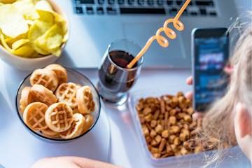Girl eats fast food and take a pictures of it on smartphone at work. Unhealthy food: chips, crackers, candy, waffles, cola. Junk food, concept.