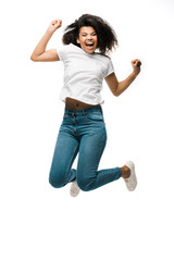 happy african american woman gesturing while celebrating and jumping isolated on white