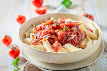 Delicious penne bolognese with herbs and bacon