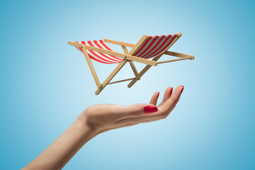 Side closeup of woman's hand facing up and levitating small striped chaise-longue on light blue gradient background.