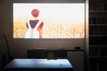 Home cinema: watching a film from a video projector in a room. Dim living room with a cinematic picture projected on the wall