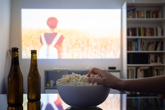 Home cinema entertainment: watching a film from a video projector in a room. Dim living room with a cinematic picture projected on the wall, human hand grabbing popcorn