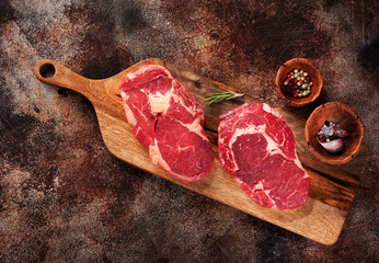 Wall Mural - Raw ribeye steaks and spices on a brown concrete background, top view.