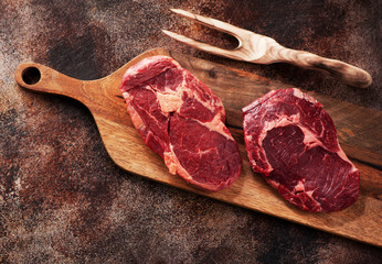 Wall Mural - Raw ribeye steaks and meat fork on wooden cutting board, top view.