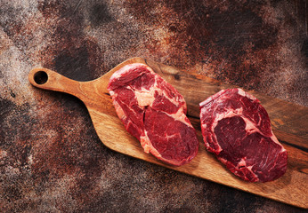Wall Mural - Raw ribeye steaks on wooden cutting board on a brown concrete background, top view.