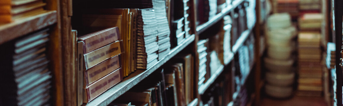 panoramic shot of retro books on wooden shelves in library