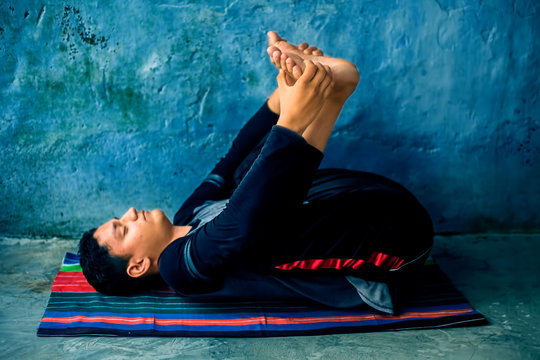 A young energetic male Caucasian teenager doing Happy baby pose or Ananda Balasana pose practice on the colorful mat along with wearing black attire.