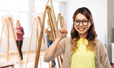 art school and creativity concept - happy asian woman in glasses or student pointing finger up over grey background