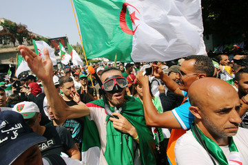 A demonstrator takes part in a protest demanding the removal of the ruling elite in Algiers