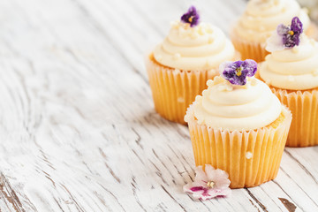 Beautiful vanilla cupcakes with buttercream icing decorated with sugar coated violet flowers. Selective focus with blurred background.