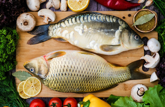 Carp and mirror carp on a cutting Board surrounded by vegetables. Fresh fish before cooking with vegetables