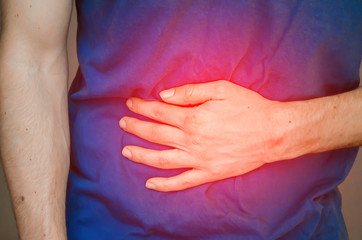 Foto op Plexiglas Beauty A man holding his stomach. Close up.