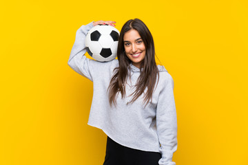 Young football player woman over isolated yellow background Wall mural