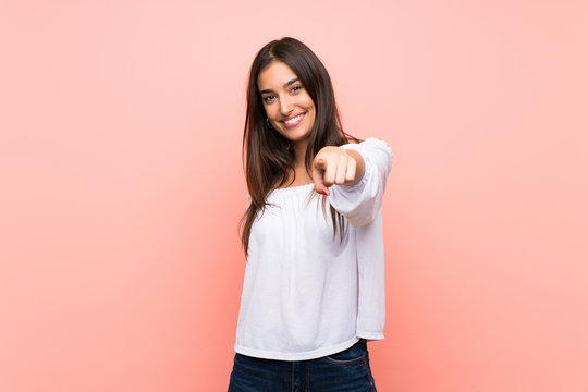 Young woman over isolated pink background points finger at you with a confident expression