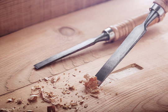 wood chisel cutting out groove in old pine plank for the door lock