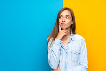 Fototapeta Young woman over colorful background thinking an idea obraz