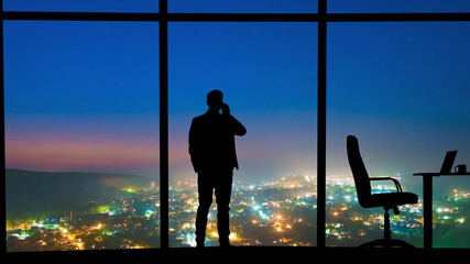 The man phones near the panoramic window on a night city background Fototapete