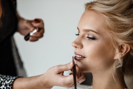 A stylist is doing a makeup on a brides face closeup.