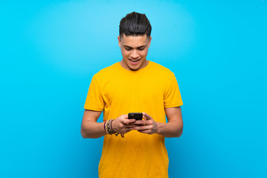 Young man with yellow shirt over isolated blue background sending a message with the mobile