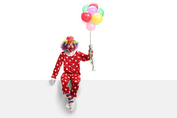 Cheerful clown sitting on a white banner and holding a bunch of balloons