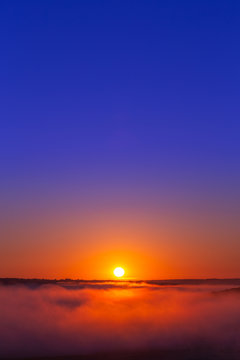 golden-blue summer sunrise over fog without clouds in minimalistic composition