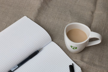 chechered clean notebook with pen and cup of coffee on the flax background on the table