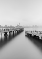View on Two piers on East River on a foggy morning with long exposure, black and white photo