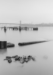 East river from the pier with view on Williamsburg Bridge on a foggy morning black and white photo