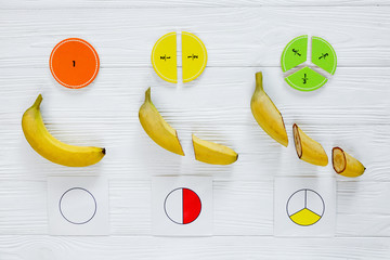 Сolorful math fractions and bananas as a sample on white wooden background or table. Interesting math for kids. Education, back to school concept. Geometry and mathematics materials.