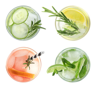 Set of glasses with different refreshing drinks on white background, top view
