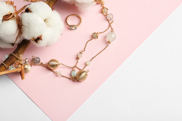 Elegant jewelry and cotton flowers on color background. Space for text
