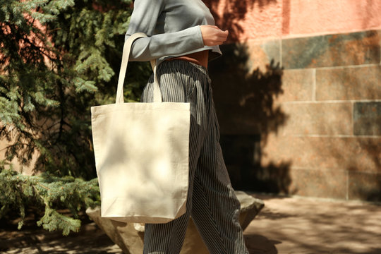 Young woman with cotton bag on city street, closeup. Mockup for design