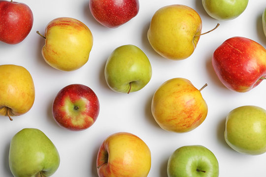 Fresh tasty apples on white background, flat lay