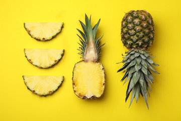 Flat lay composition with cut and fresh juicy pineapples on color background