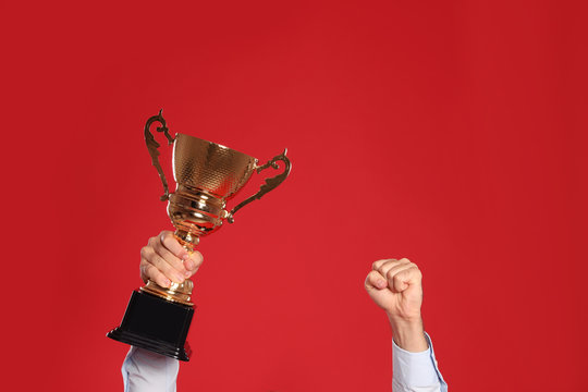 Young man with gold trophy cup on red background, closeup. Space for text