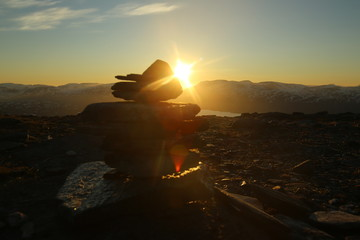 Midnight sun seen from the peak of Nuolja in Northern Sweden, with defocused cairn