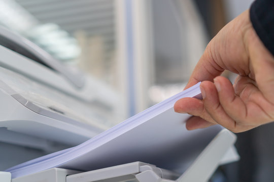 Business printer / printing documents in office concept: Businessman press white paper in laser printed cartridge feeder, scanner machine for copy document to report in busy modern offices background