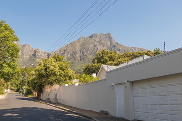 Street in the town of Claremont, Cape Town, South Africa. Sunny weather and panorama of Table Mountains.