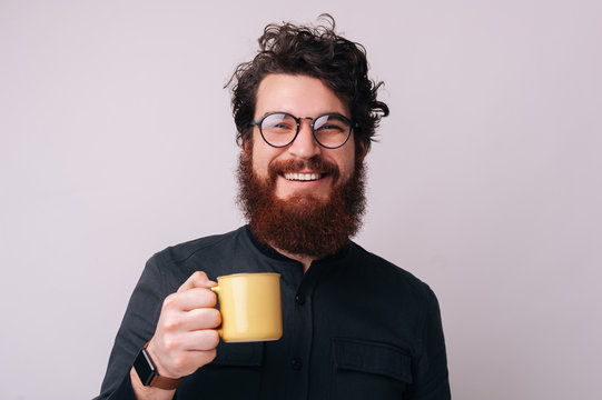 Photo of some cheerful bearded guy wearing glasses, loooking at camera and holding a mug with coffee, over isolated background