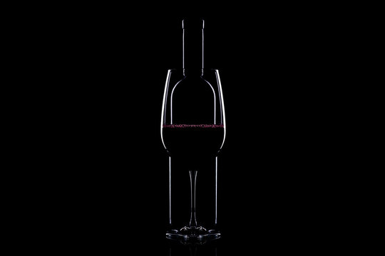Elegant red wine glass and a wine bottle over black background