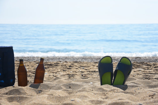 Cold beer and slippers on sand at beach. Summer vacation concept, enjoy at beach