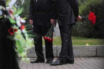 Men gather at a cemetery before the funeral of Russian sailors killed in a fire on a submarine in Saint Petersburg