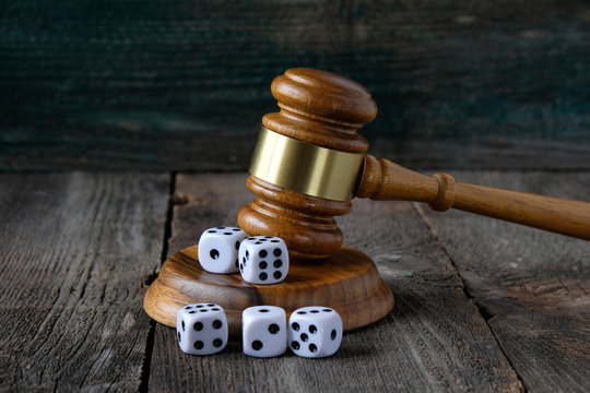 Concept of legal regulation of gambling, justice gavel and dice on the background of an old wooden table.