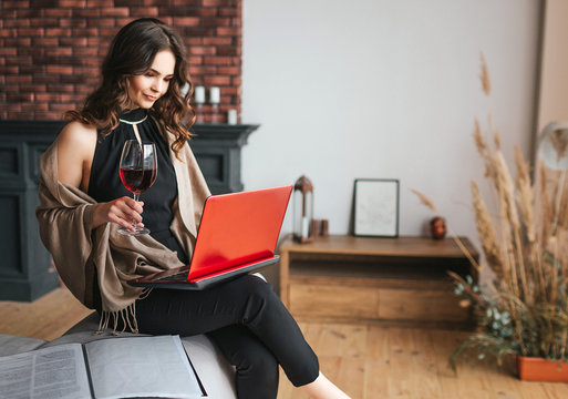 Young businesswoman work at home. Sit and hold laptop on knees. Galss of red wine in right hand. Busy attractive woman remote work. Typing on keyboard.