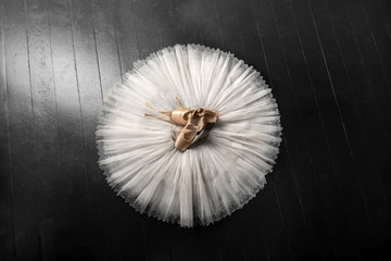 Pointe shoes. Peach shoes, ballet shoes with ribbons on a white tutu in a dance studio. Advertising ballet school. Professional ballerina outfit.