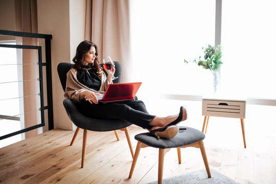 Young businesswoman work at home. Sitting in chair and drink red wine from glass. Remote work. Red laptop on knees. Alone in living room. Daylight.