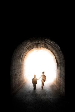 Two little siblings walking into the light