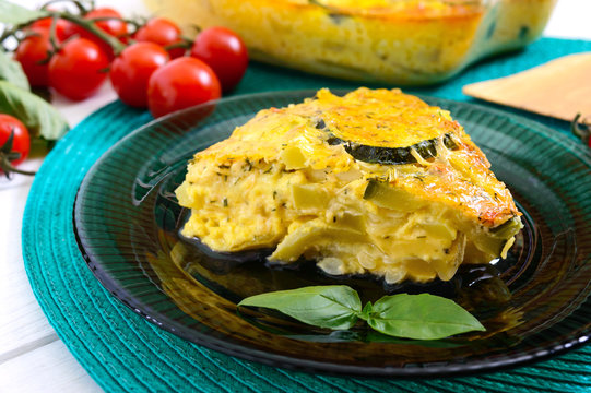 Zucchini, cheese, eggs, cream and greens casserole on a white wooden background. Portion of casserole on a plate. Tasty healthy dish.