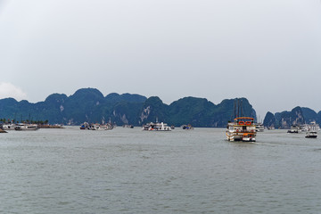 A lot of tourist junks floating to limestone rocks at Ha Long Bay